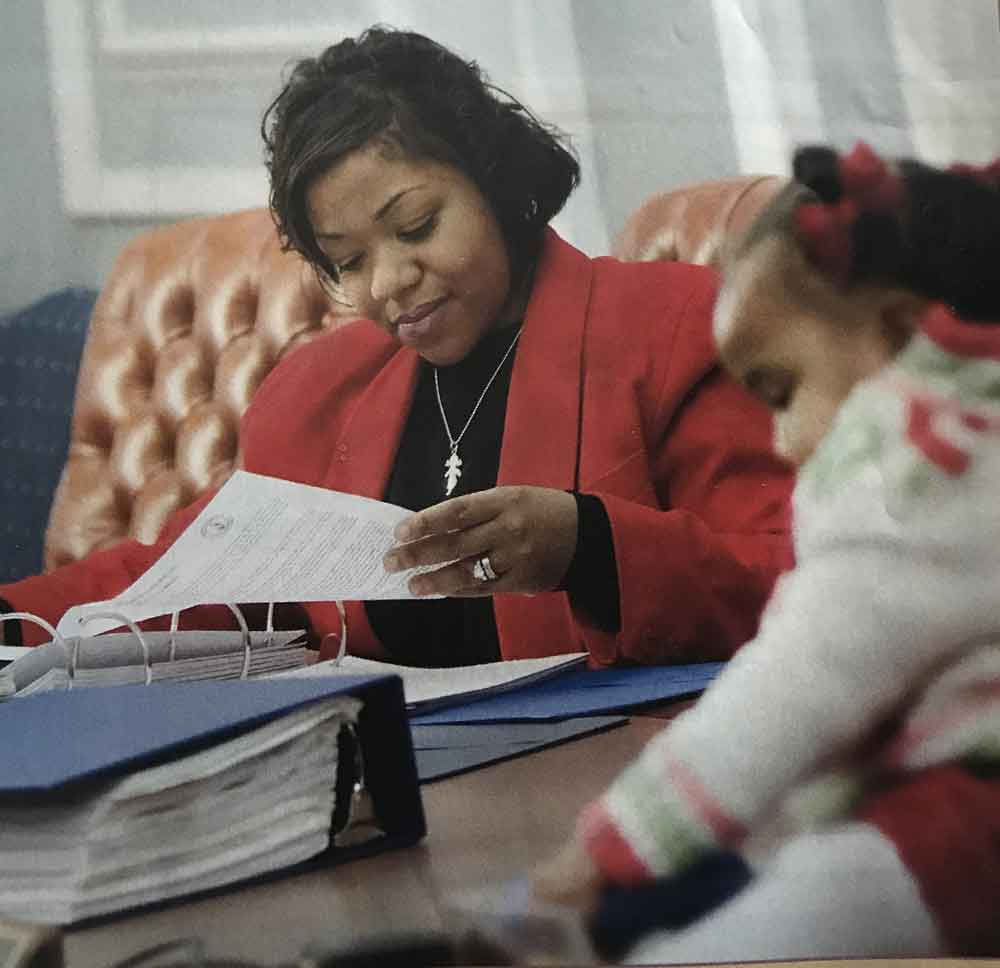 Tameika in the office working with daughter looking on